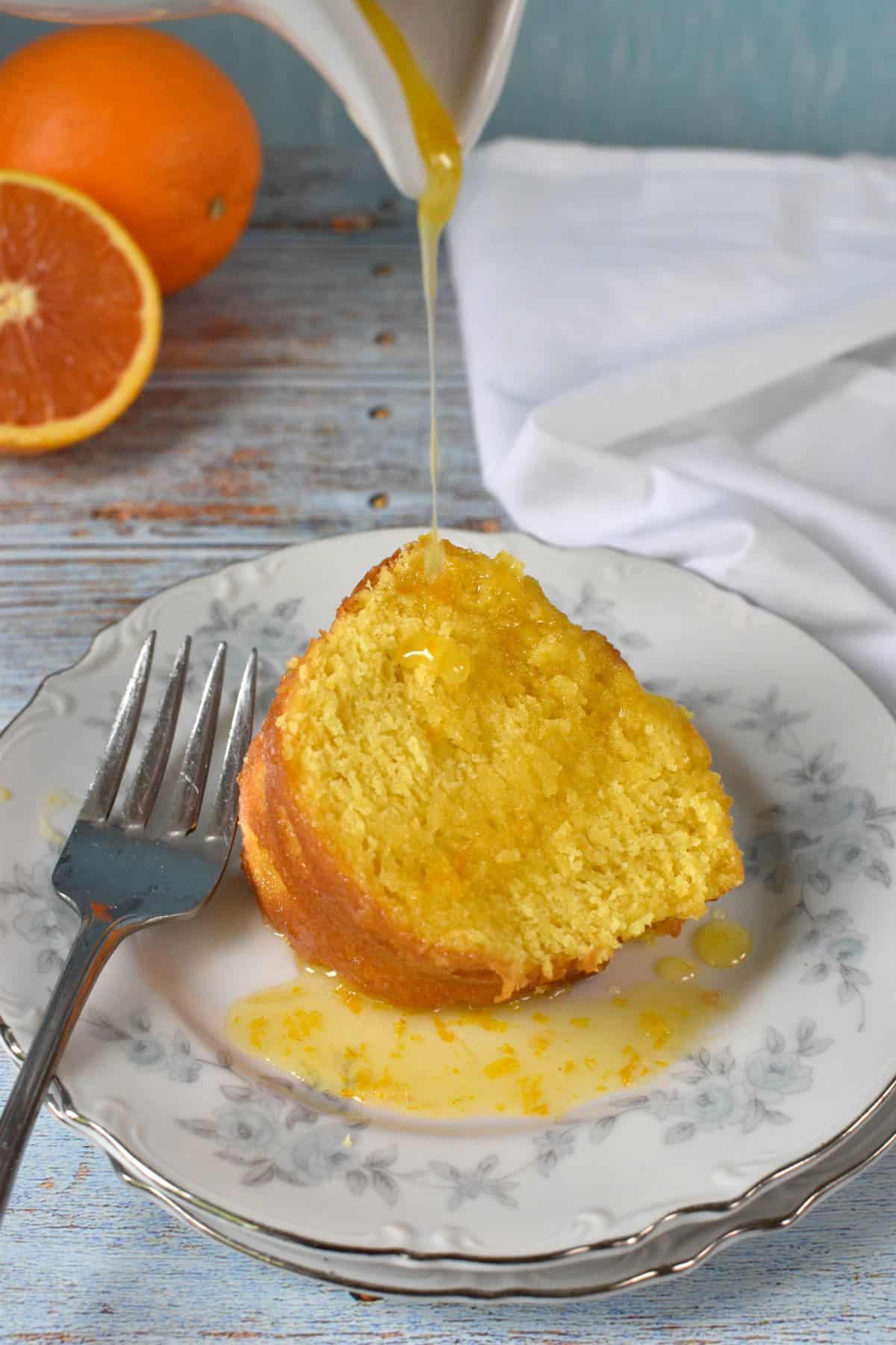 Derramando calda de laranja sobre uma fatia de bolo de laranja
