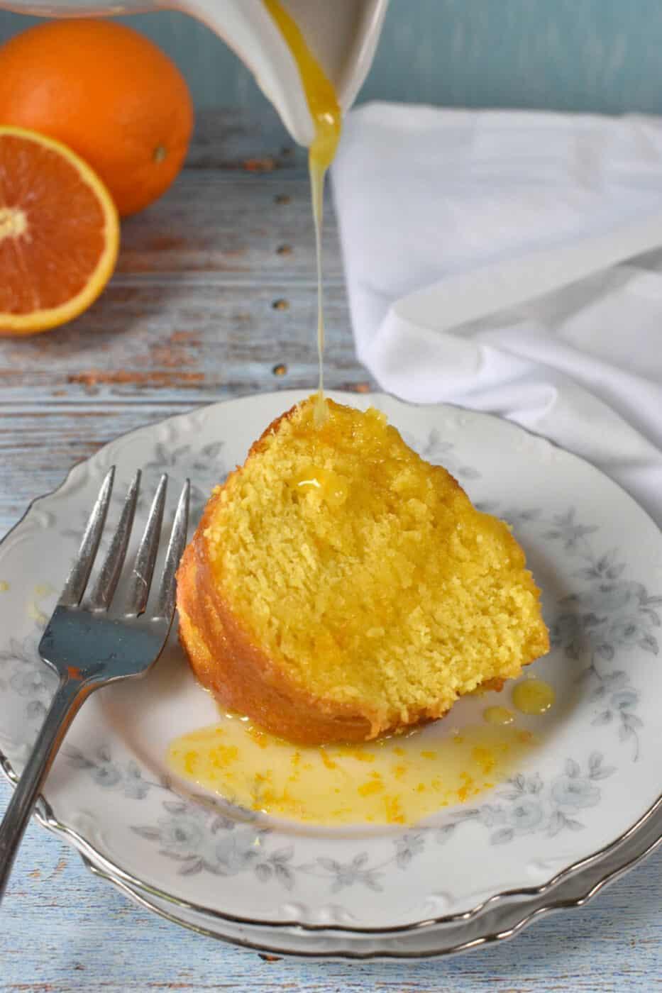 Drizzling orange glaze on a slice of orange cake