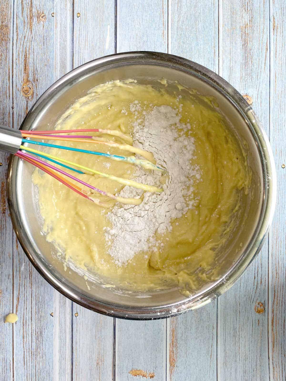 Farinha e fermento sendo acrescentados à mistura de laranja em uma tigela