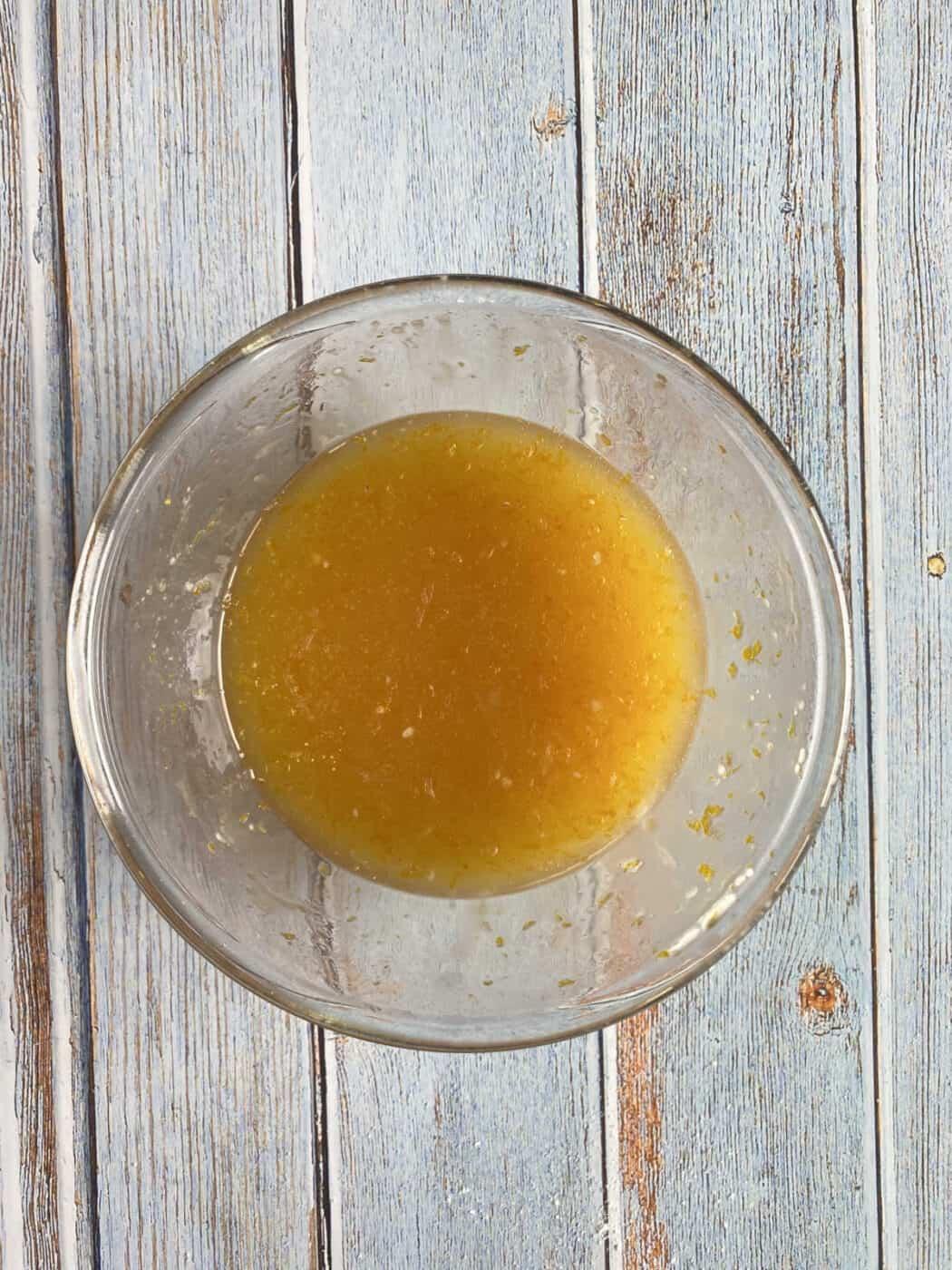 orange juice, orange zest and powdered sugar, mixed in a glass bowl