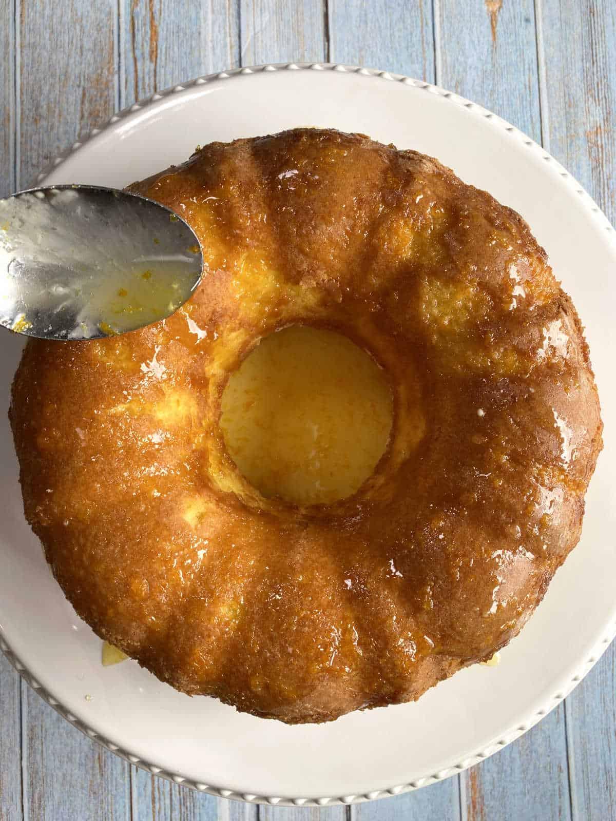 Jogando a calda de laranja por cima do bolo assado