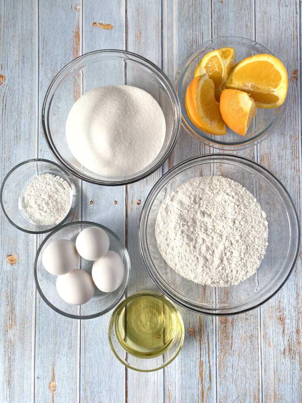 Orange wedges, flour, sugar, eggs, oils and baking powder in glass bowls