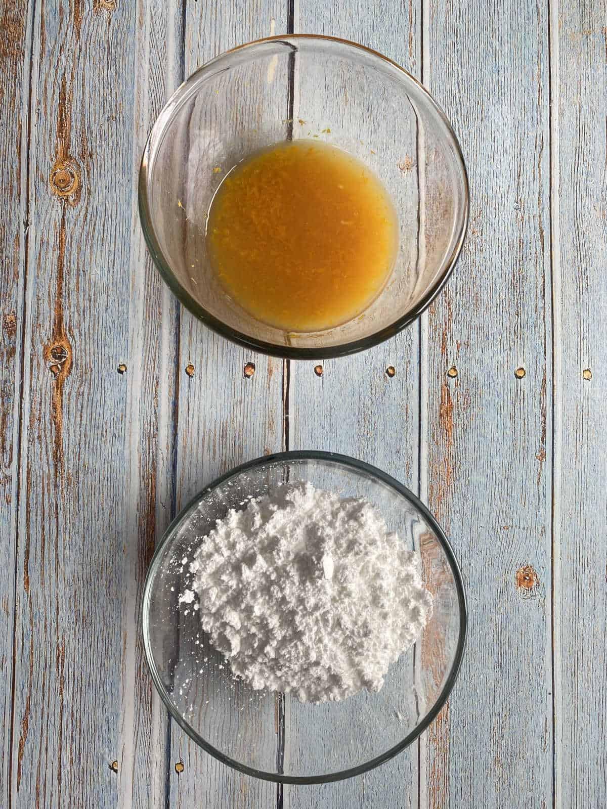 açúcar de confeiteiro e suco de laranja com raspas da casca de laranja, separados em tigelas de vidro