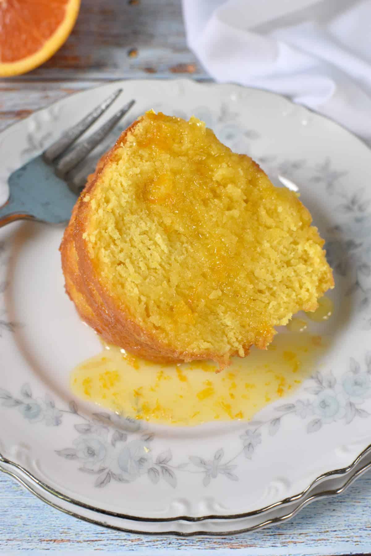 fatia de bolo de laranja com calda de laranja em um prato com garfo