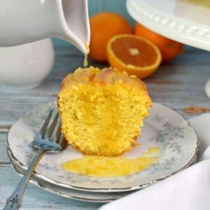 derramando calda de laranja sobre uma fatia de bolo de laranja em um prato
