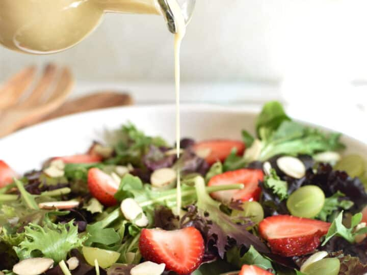 Asian Salad dressing being poured over a salad with strawberries, green grapes and almonds