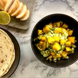 Mango salsa with cucumber and shallots in a black bowl