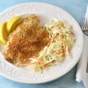 Baked tilapia fillet on a white plate with salad and lemon wedges