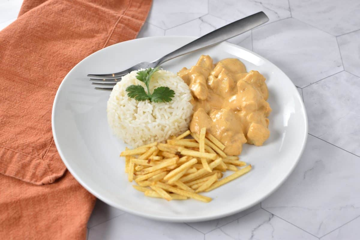 brazilian stroganoff, rice and potatoes sticks on a plate