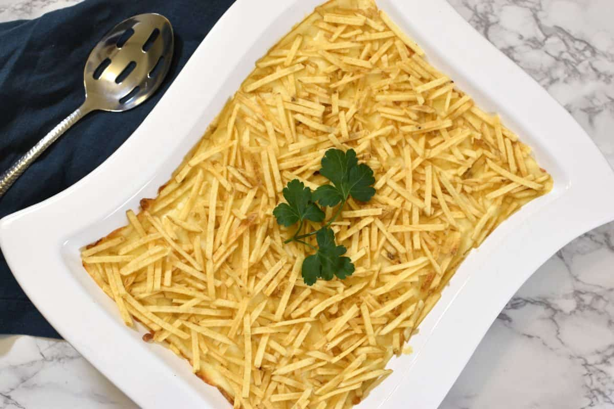 Shredded chicken with creamy sauce, covered with cheese and potato sticks
