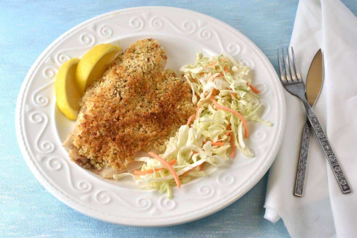 Tilapia with panko crust on a plate with lemon wedges and salad