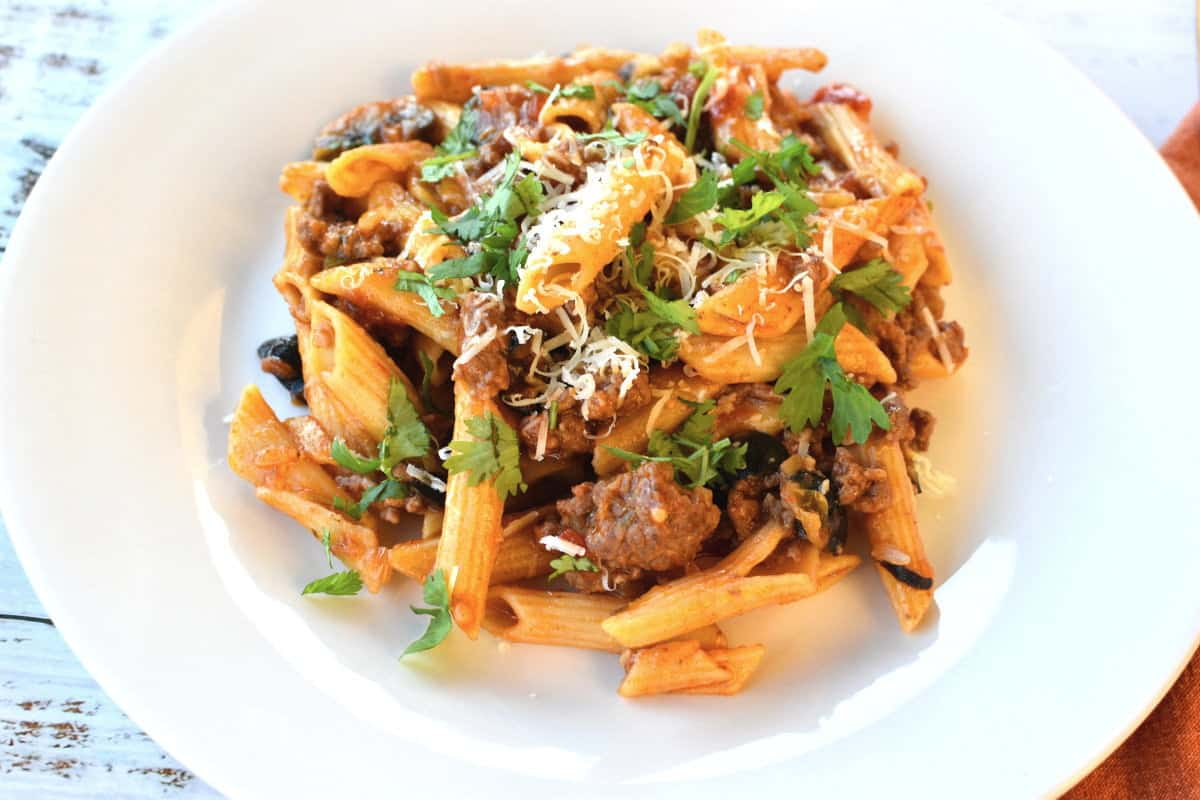 Penne pasta with taco seasoning, ground beef and parsley on a white plate