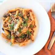 penne com carne moida, molho vermelho, coentro, cogumelos e azeitonas no prato branco com talheres