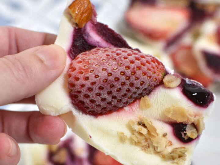Frozen Yogurt bark. Hand holding it. Topped with strawberry, jam and granola