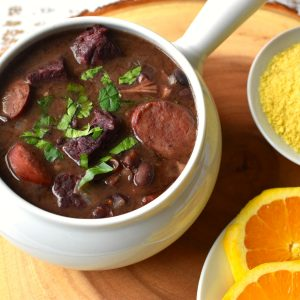 Brazilian Feijoada (black bean stew) served with farofa and orange slices