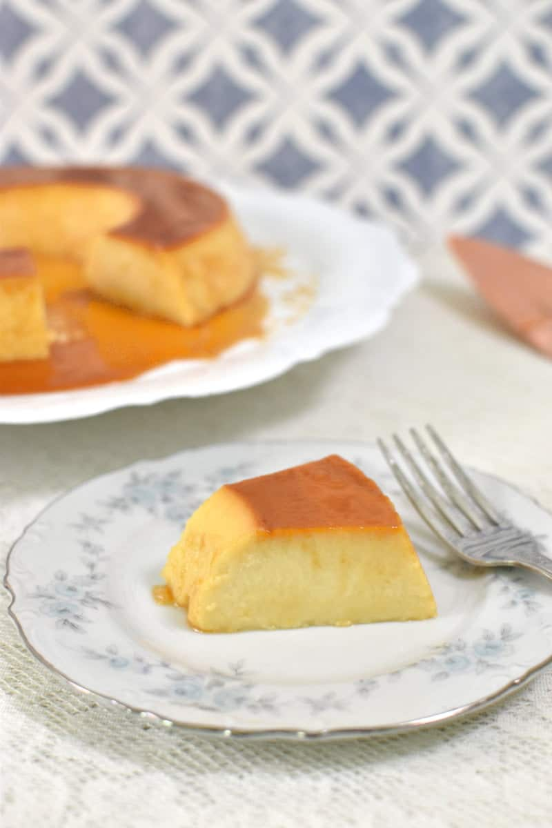 Brazilian flan slice, with the whole flan in the back