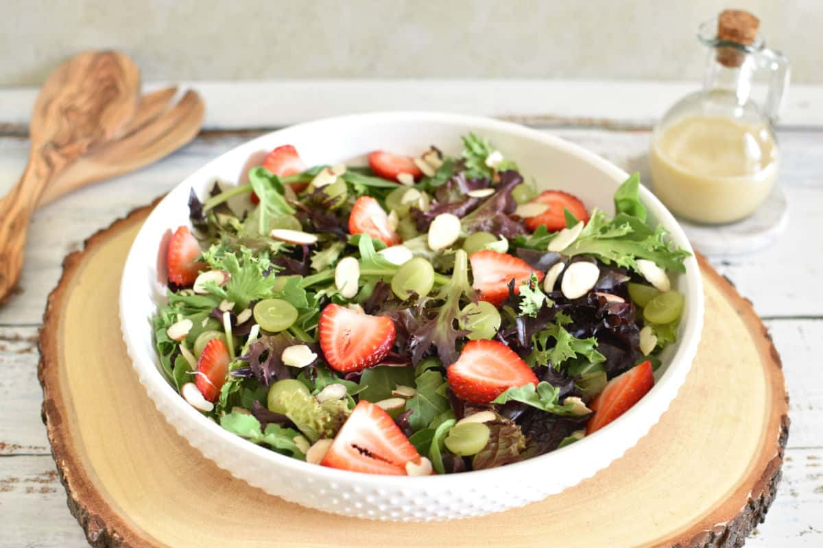 Molho asiático para salada e salada de folhas mistas com morangos, uvas e lascas de amêndoas