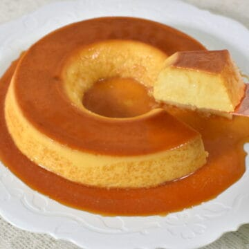 Cutting a piece of Brazilian Flan on a white serving dish
