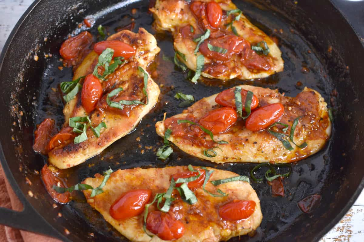 pan seared chicken breasts with grape tomatoes and basil in a iron skillet