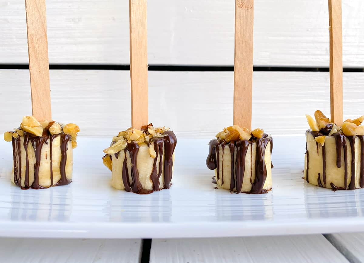 Chocolate covered banana with walnuts on a stick