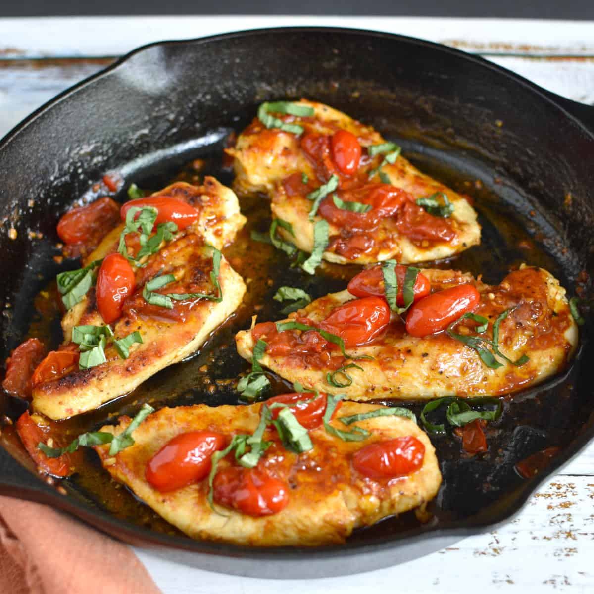 pan seared chicken breasts with tomatoes and basil in an iron skillet