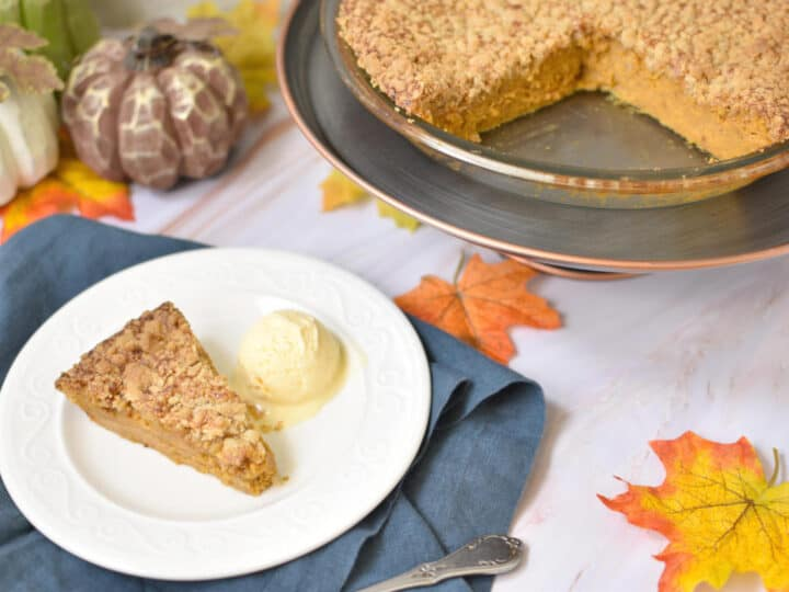 slice of pumpkin pie with ice cream on a white plate, and a pie on the background