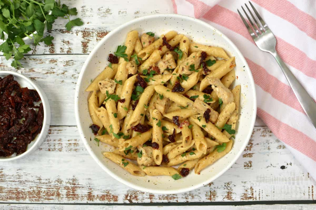 pasta, chicken, sundried tomatoes, parsley with creamy sauce in a plate