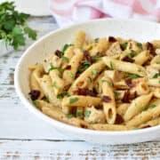 Pene com frango, tomate seco, salsinha e molho cremoso de queijo em um prato branco. Feito na panela de pressão