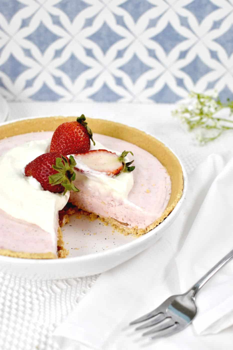 Frozen strawberry pie with whipped cream and strawberries on top, missing one slice