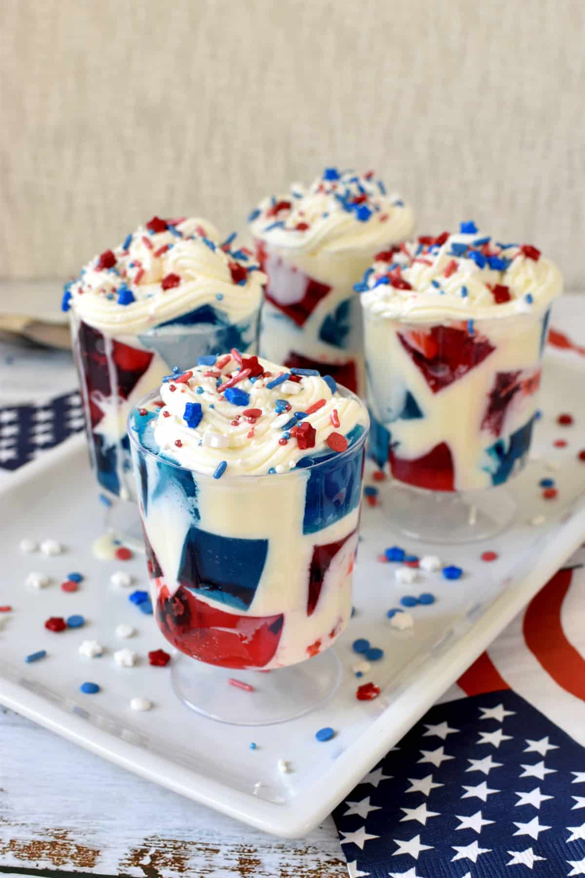 blue and red Jell-O squares in a cups with a white cream and topped with whipped cream and shaped sprinkles