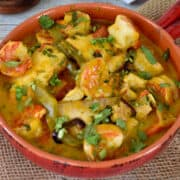 fish, shrimp, vegetables and cilantro with sauce in a clay pan.