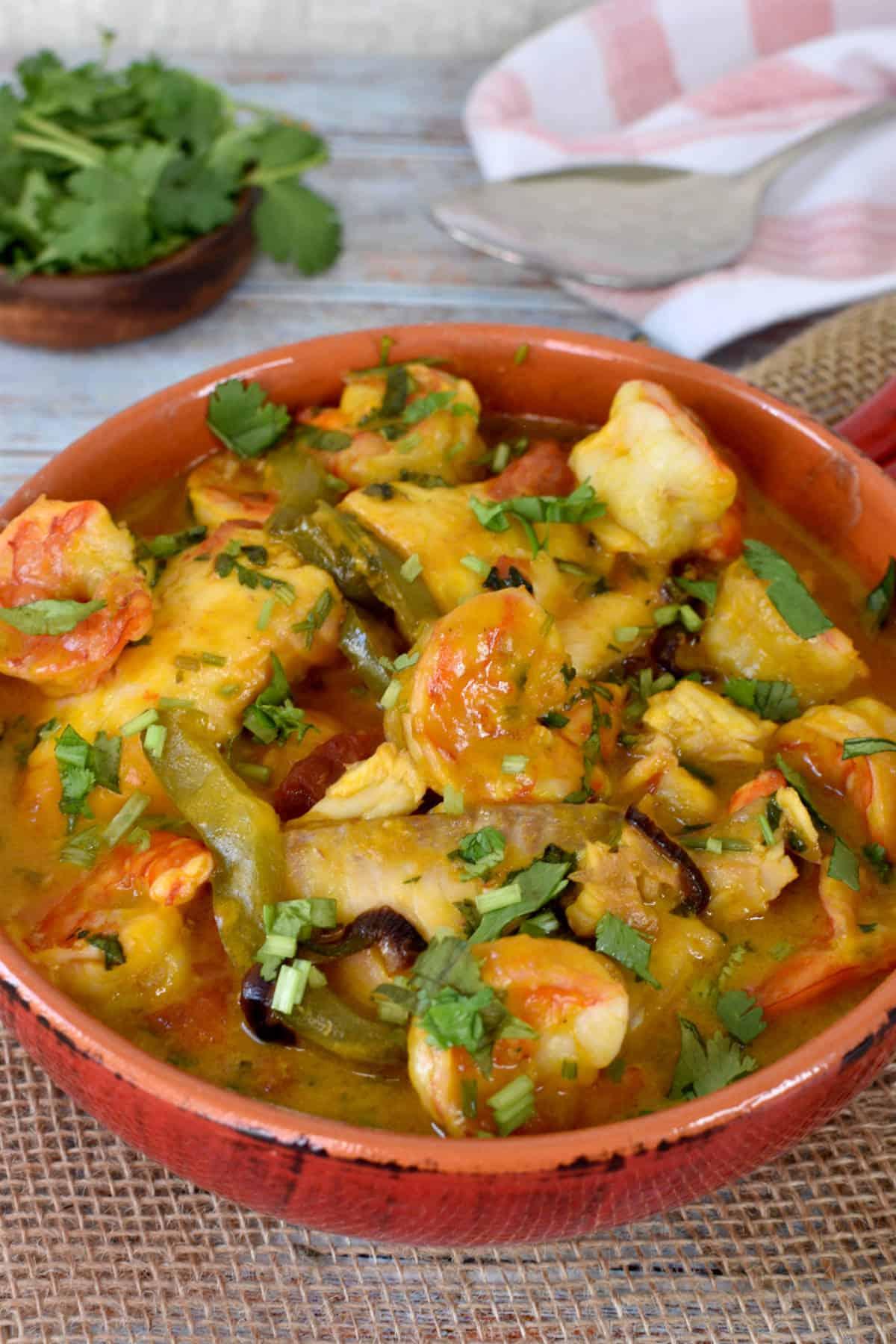 peixe, camarão, legumes e cilantro, com molho em uma panela de barro