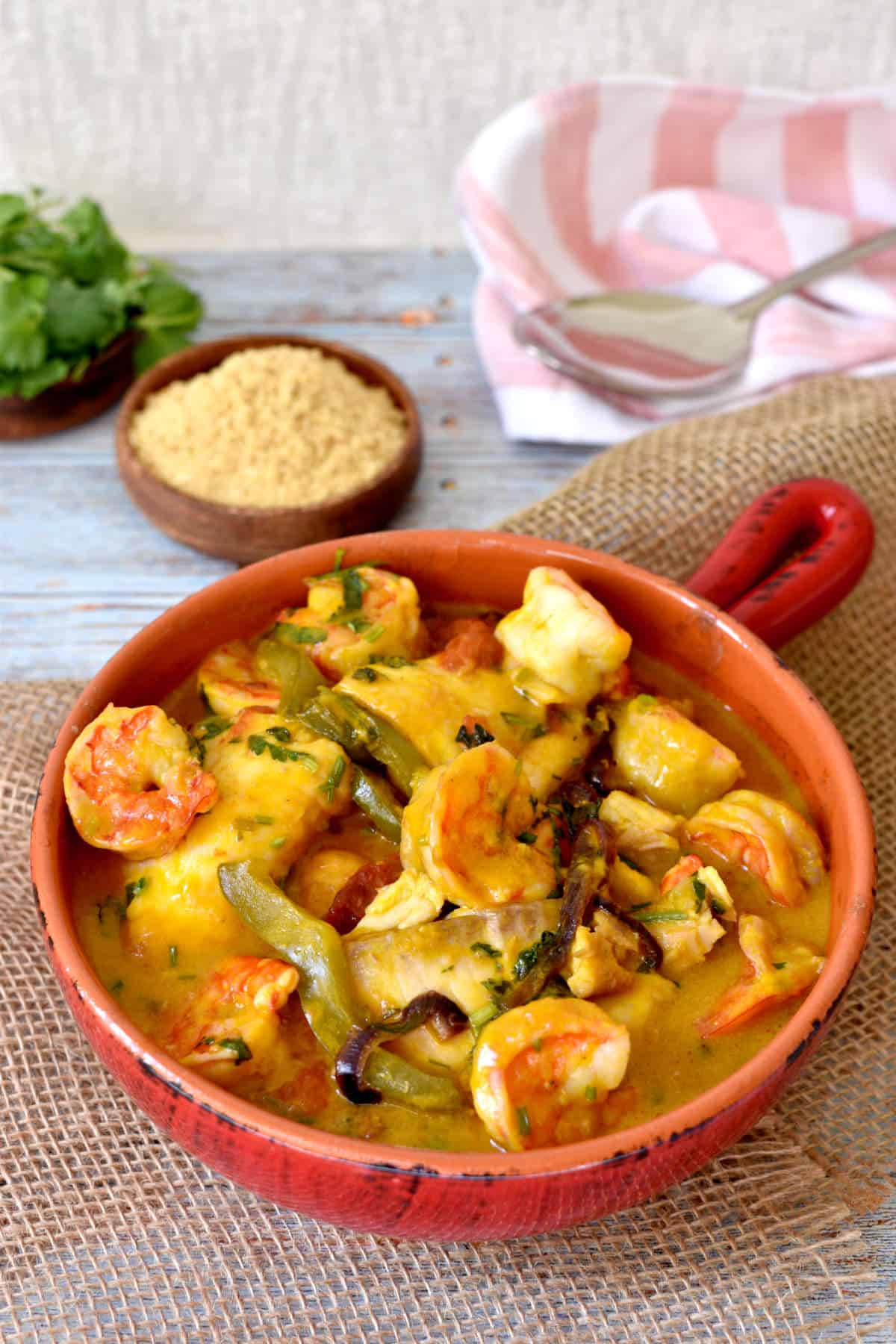 fish, shrimps, vegetables and cilantro cooked as a stew in a clay pan.