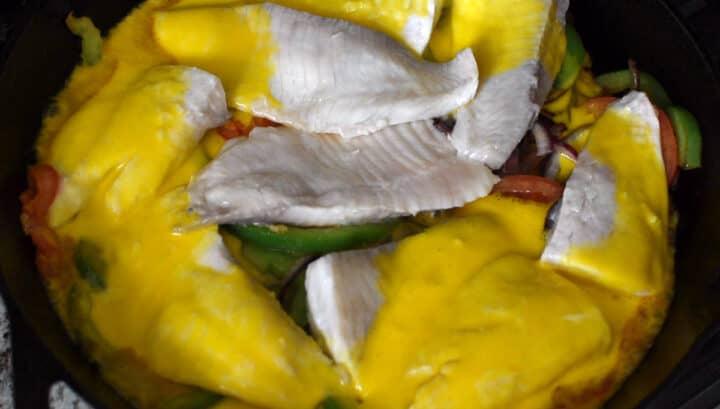 molho de leite de coco com azeite de dendê sobre filés de peixe e legumes