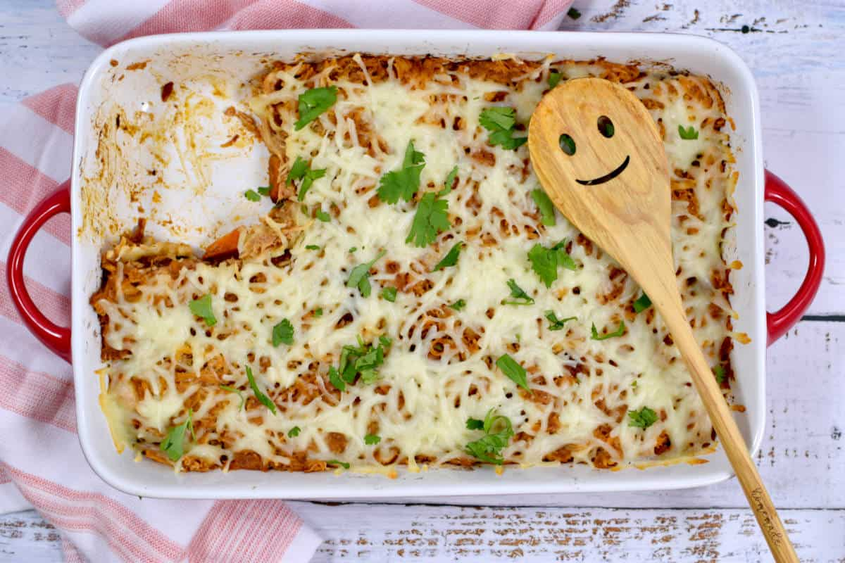 chicken and sweet potato casserole, missing a piece, with a smiley wooden spoon on top