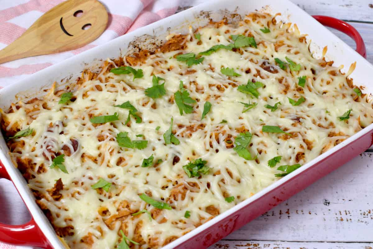 chicken and sweet potato casserole topped with cheese and parsley, with a wooden spoon on the side