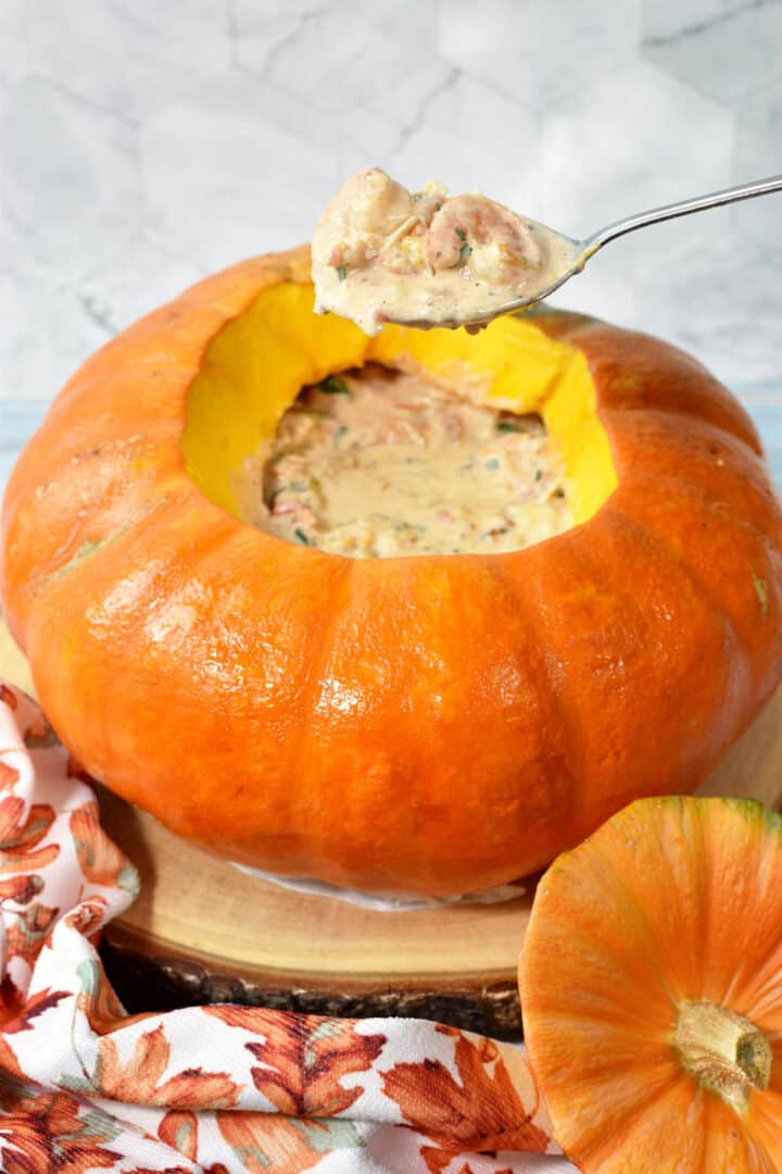 A spoonful of creamy shrimp, out of a pumpkin filled with creamy shrimp stew