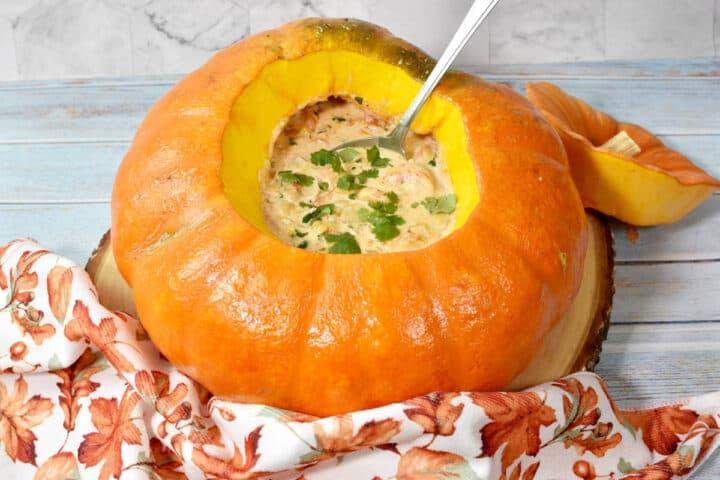 shrimp chowder in a Cinderella pumpkin with a spoon inside